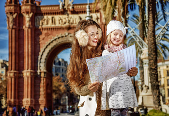 happy mother and daughter in Barcelona, Spain looking at map