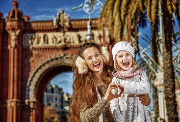 mother and child in Barcelona showing heart shaped hands