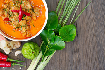 Chicken Panang curry in the white bowl and fresh spice on gray wooden background, Thai food