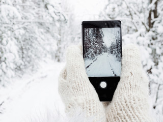 Girl is holding a mobile phone in woolen mittens in the winter against a background of trees in the snow