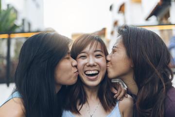 Asian friends women having fun in the street.