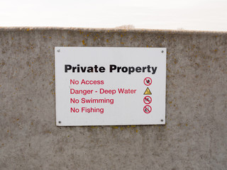 private property sign on grey sea wall barricade no permission