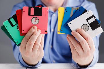 Male hold floppy disk in hands, retro storage