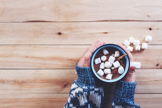 a cup of hot chocolate with marshmallow in women hands
