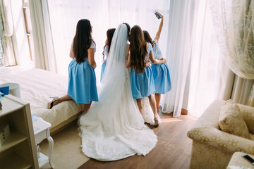 Beautiful bride and bridesmaids in a turquoise dresses are taking pictures before wedding ceremony. Rear view. Artwork.