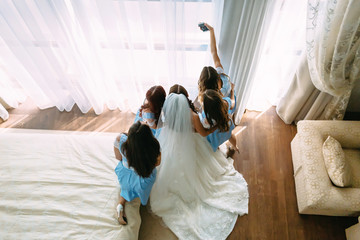 Beautiful bride and bridesmaids in a turquoise dresses are taking pictures before wedding ceremony. Top view. Artwork.