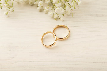 Two golden wedding rings with flower decorations