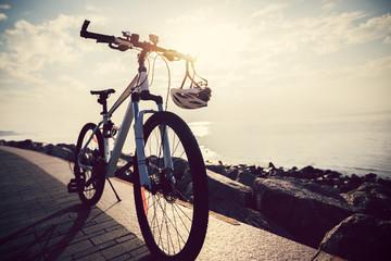mountain bike with helmet on sunrise seaside