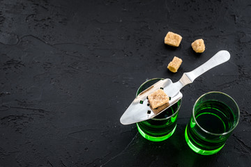 Traditions of drinking absinthe. Special spoon and sugar cubes near shots on black background top view copy space