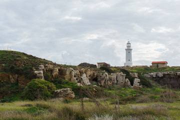Photo of lighthouse on hill in background of cloudy sky