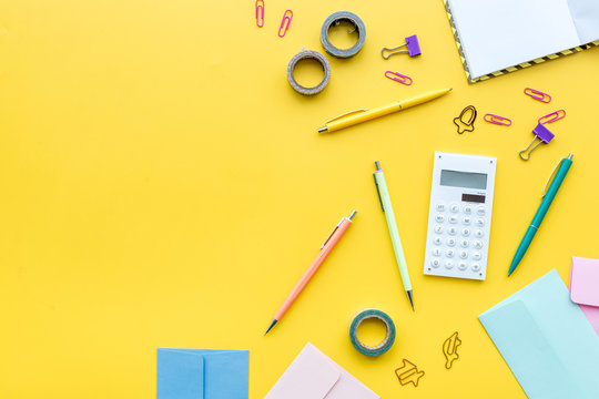 Scattered stationery on student's desk. Yellow background top view copy space