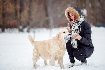 Photo of smiling woman squatting next to labrador with toy in teeth in winter