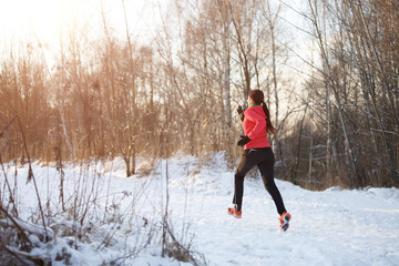 Photo from back of woman in sports uniform on morning run in winter forest