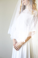 Young pretty blond woman wearing wedding dress indoors