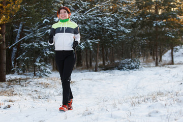 Image of smiling sportswoman in sneakers on morning run against background of trees in winter