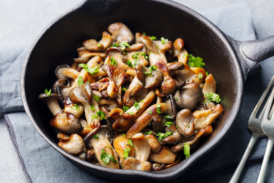 Fried mushrooms with fresh herbs in black cast iron pan.
