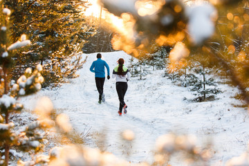 Picture from back of running sports woman and man in winter park
