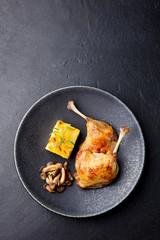 Duck legs confit with potato gratin and mushroom sauce . Restaurant serving.