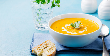 Pumpkin and carrot soup with cream and parsley on blue stone background. Copy space.