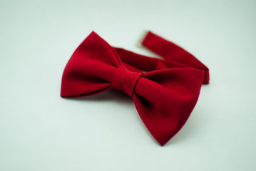A stylish and well-designed red bow-tie on a white background; isolated