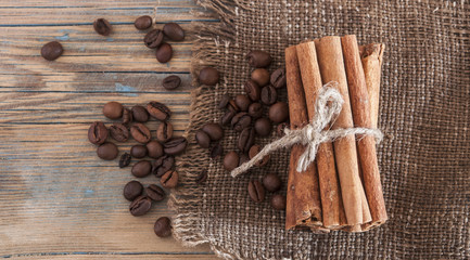 Pile of coffee beans, cinnamon sticks on old wood.