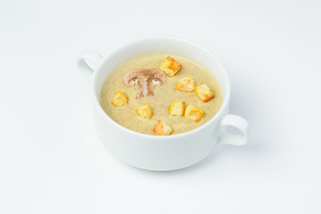 Mushroom cream soup with croutons on a white background