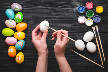 Happy Easter. Hands painting eggs for Easter holiday on wooden table.