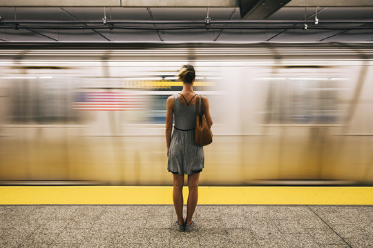 Young woman waiting for subway train in New York City