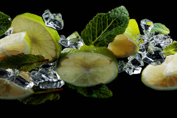 Lime pieces with leaves of peppermint on black background.
