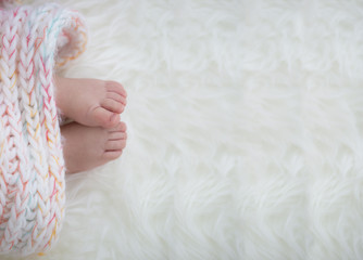 baby feet in blanket, copy space. selected focus
