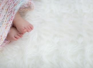 baby feet in blanket, copy space. selected focus