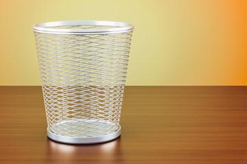 Empty metal garbage bin on the wooden table, 3D rendering