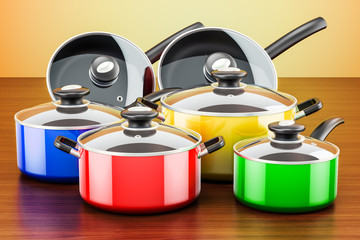 Set of colored cooking kitchen utensils and cookware. Pots and pans on the wooden table. 3D rendering