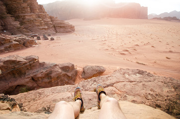 Jordan national park Wadi Rum desert. Beautiful view and panoramatic picture of man legs and outdoor shoes. Natural background. Sunset in a desert.