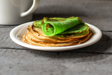 Green pancakes in a white plate