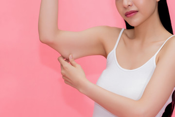 Young attractive Asian woman pinching excess fat and cellulite in her upper arms as she lacks exercise and healthy lifestyle.