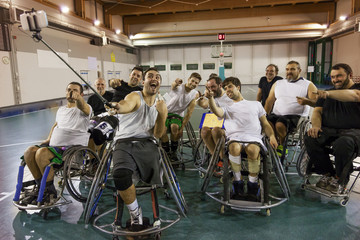 group of smiling disabled basketball players take a selfie