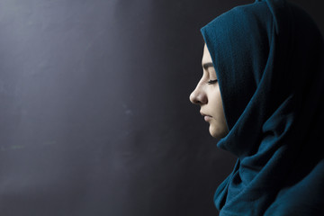 A Muslim woman with closed eyes, on a black background. Arab girl in hijab in profile.