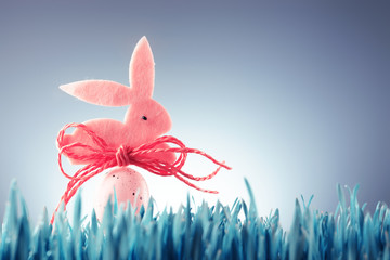 Easter background concept with pink bunny figure and egg on wood stick in green grass