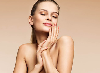 Sensual woman with clean healthy skin touching her face. Photo of beautiful woman of european appearance on beige background. Skin care and beauty concept
