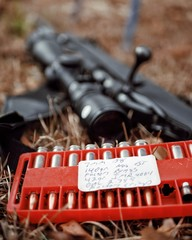 Hand loaded cartridges in a red container with a black 7mm rifle backdrop.