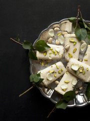 Pista kulfi, Indian ice cream on serving plate with ice cubes, pistachios, rose petals, tree branches with green leaves on black background, top view. Traditional Rajasthani Indian cuisine.