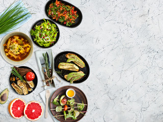Healthy vegetarian meals - vegetables, salads, soup, fruits, herbs served on marble table. Top view. Copy space.