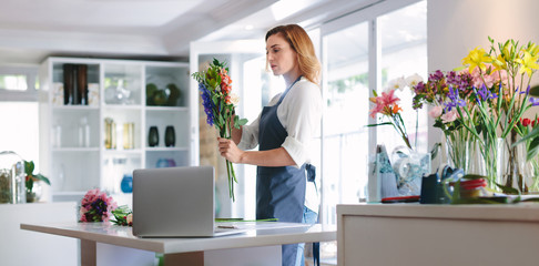 Female florist at work creating a bouquet