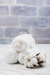 White cotton towels and branch of cotton on wooden table