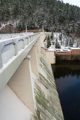 Concrete Brezova dam with hydroelectric power plant and road to Karlovy Vary, snowy winter day, Czech Republic