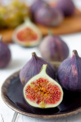 Half of fig fruit on a brown ceramic plate over white wooden table.