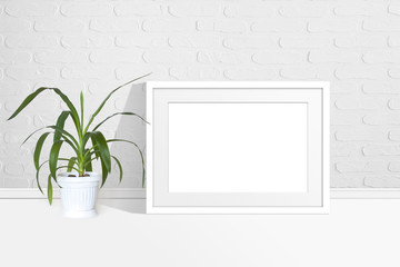 Photo frame mock up and Yucca plant in flower pot near white bricks wall.