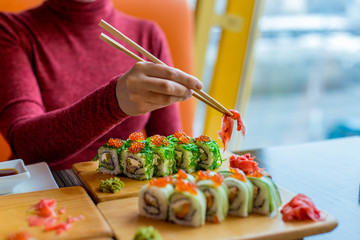 Woman eating sushi rolls at the table