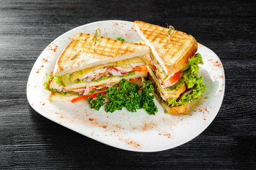 Sandwiches with chicken and Bacon on a black wooden background